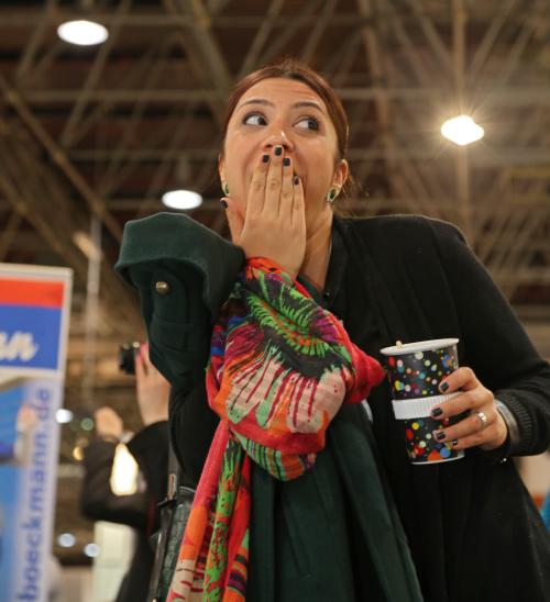 Eine junge Frau hält sich mit einem verschmitzten Lächeln die rechte Hand vor dem Mund. In den linken Hand hält Sie einen Kaffee Becher.