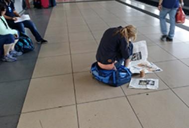Frau liest Zeitung auf Bahnsteig