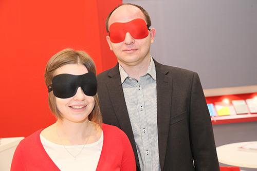 Links: junge Frau mit schwarzer Augenmaske.  Rechts: Mann mit roter Augenmaske. Beide lächeln, die Frau ein wenig mehr.