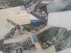 Verschiedene Postkarten mit Stadt- oder Küstenansicht, liegen verteilt übereinander. Es sind hautpsächlich schwarz / weiße Abbildungen zu sehen, beschriftete Rückseiten, teilweise bereits vergilbt und mit verblasstem Poststempel.