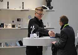 Produktausstellung. Zwei Geschäftsmänner begrüßen sich per Händedruck.