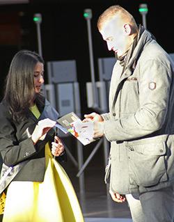 Eine junge Frau mit langen schwarzen Haaren im gelben Kleid und schwarzem Blazer steht einem jungen Mann gegenüber, der in seinen Händen einen Flyer hält. Beide blicken auf diesen Flyer.