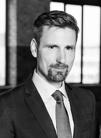 Schwarz weißes Porträt Foto eines Mannes mittleren Alters mit dunklen Haaren und dunklen Augen sowie einem Henryquatre Bart. Er trägt einen dunklen Anzug und ein weißes Hemd mit Krawatte. Sein Blick seriös und leicht lächelnd.