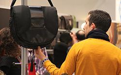 Mann prüft Materialbeschaffenheit einer Tasche