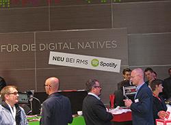 """Vor einer braunen Panel Wand mit der Aufschrift """"Für die digital natives"""" und dem Untertitel """"neu bei RMS Spotify"""" stehen verschiedene Menschen in Business Kleidung. Manche unterhalten sich, manche laufen lediglich dran vorbei."""
