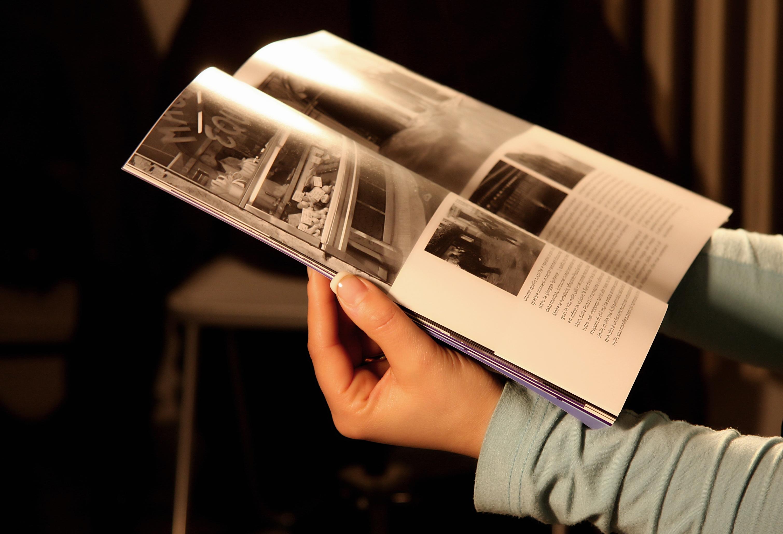Zarte Hände, vermutlich die einer Frau, halten eine Zeitschrift mit Illustration und Text.