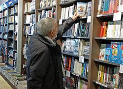 Mehrere Regale mit Bücher gefüllt. Ein älterer Herr greift nach einem Buch.