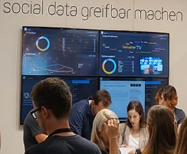 Menschen vor grafisch dargestellten Onlinedaten
