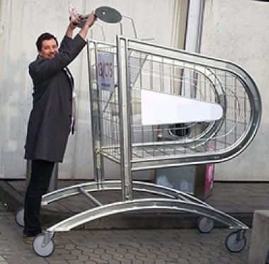 Mann vor einem überdimensionierten Einkaufswagen