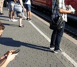 Bahnreisende lesen Zeitung und Handy